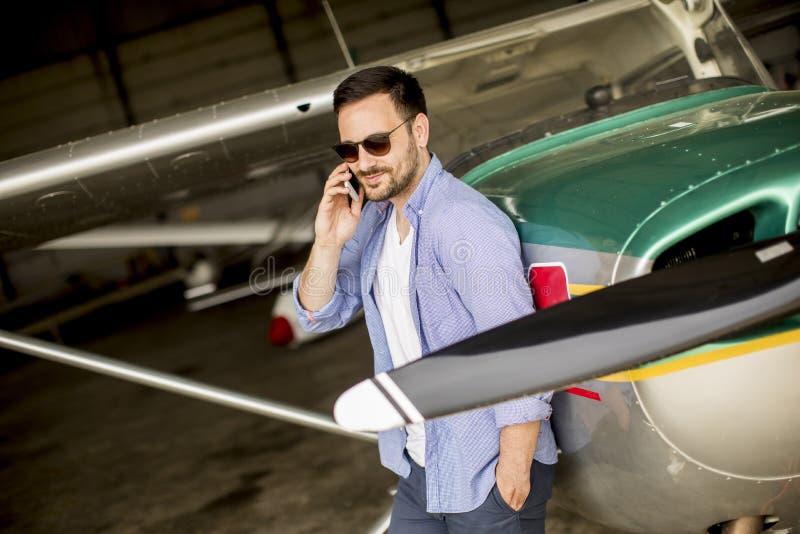 Jeune avion de vérification pilote beau dans le hangar et le m d'utilisation image libre de droits