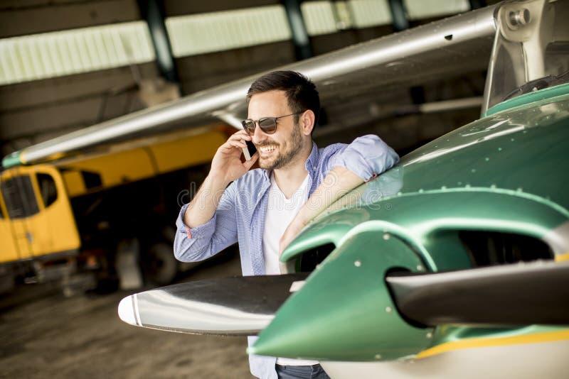 Jeune avion de v?rification pilote beau dans le hangar et le m d'utilisation photos libres de droits