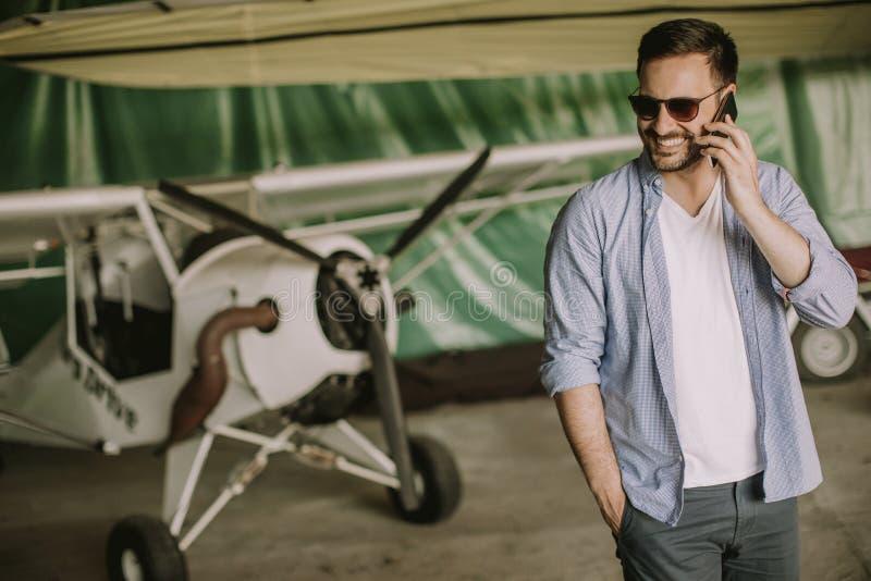 Jeune avion de v?rification pilote beau dans le hangar et le m d'utilisation images libres de droits