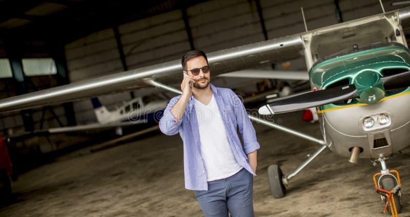 Jeune avion de v?rification pilote beau dans le hangar et le m d'utilisation photo stock