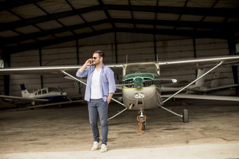 Jeune avion de v?rification pilote beau dans le hangar et le m d'utilisation photos stock