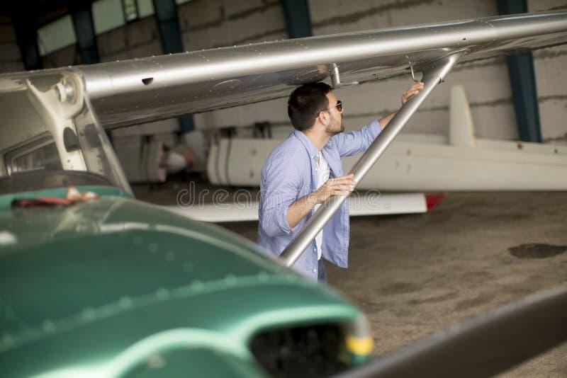 Jeune avion de v?rification pilote dans le hangar photographie stock libre de droits