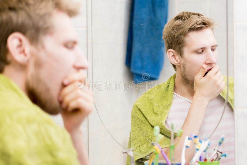 Jeune bâillement barbu d'homme devant le miroir dans la salle de bains image libre de droits