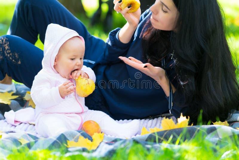 Jeune bébé mordant dans une pomme photos stock