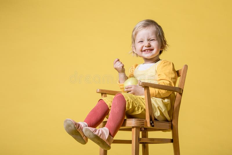 Jeune b?b? dans la robe jaune sur le fond jaune photographie stock libre de droits