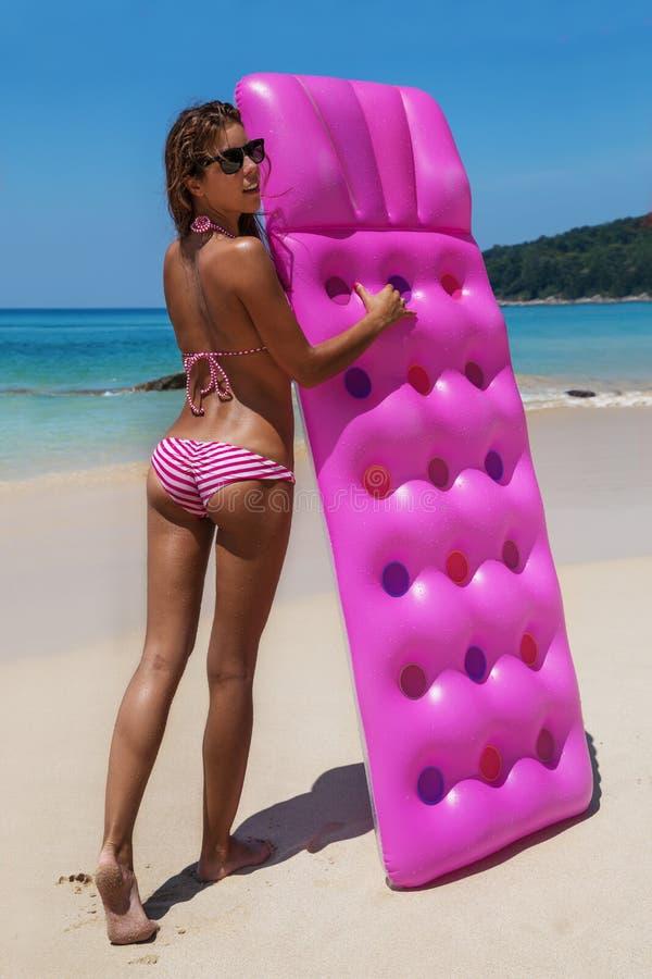 Jeune bain de soleil mince de femme avec le matelas d'air sur la plage tropicale image libre de droits