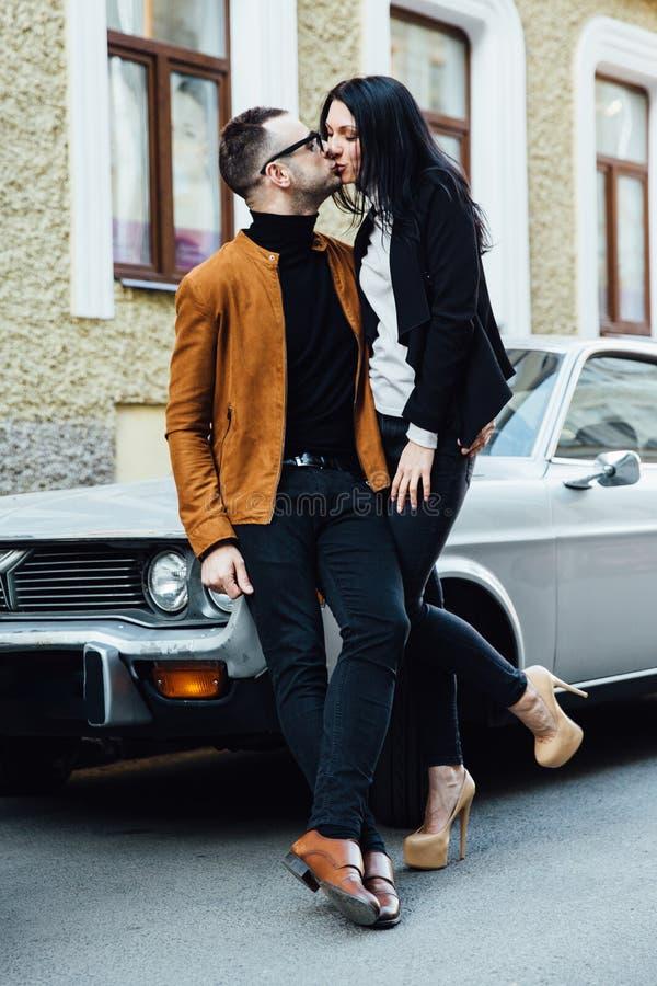 Jeune baiser de couples près de la voiture image stock