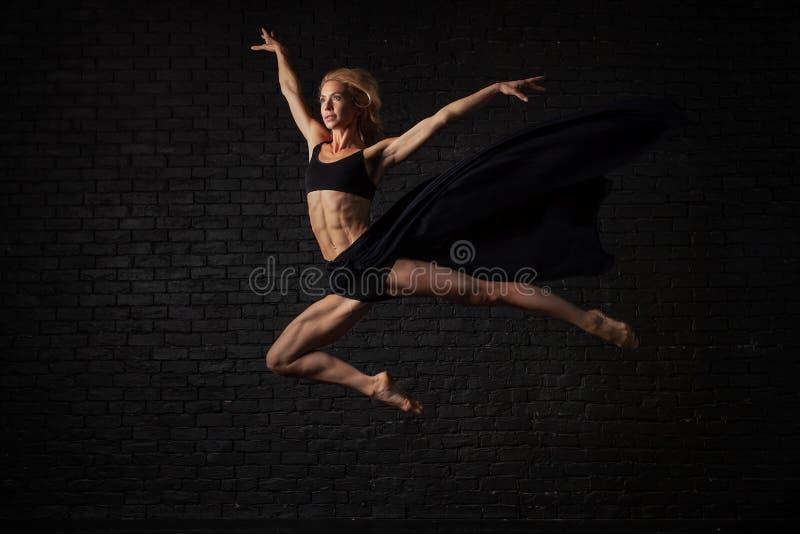 Jeune ballerine blonde dans des danses et des sauts de sous-vêtements de vêtements de sport dans un studio avec la brique noire s photographie stock libre de droits