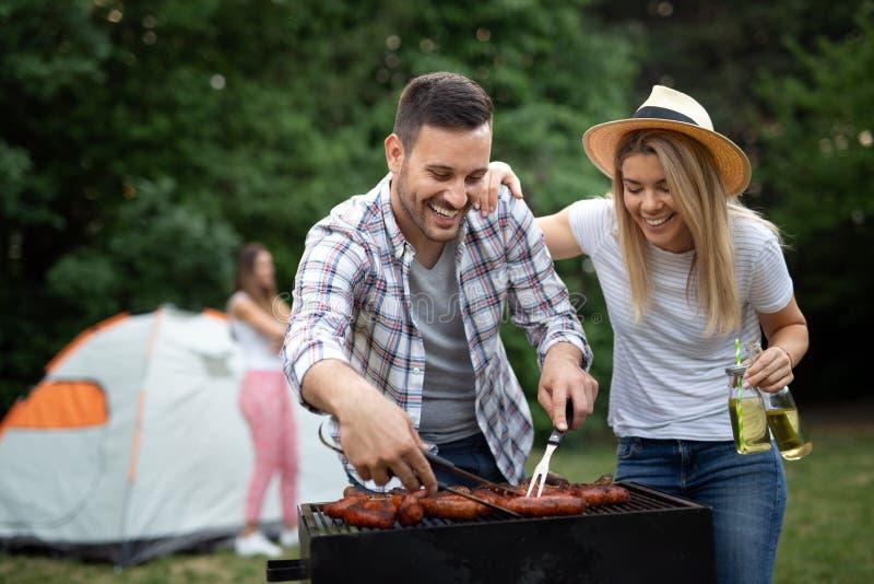 Jeune barbecue femelle et masculin de cuisson de couples en nature image stock