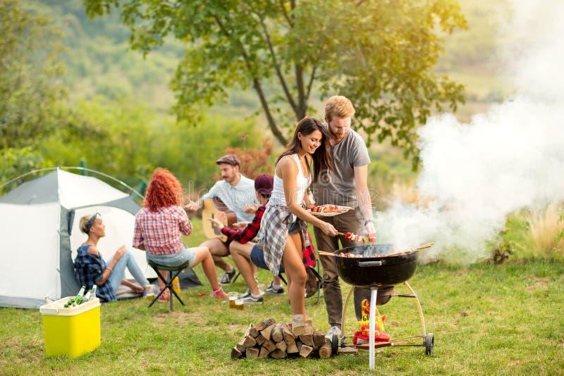 Jeune barbecue femelle et masculin de cuisson de couples image stock