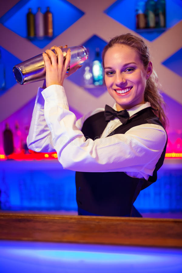 Jeune barmaid avec le dispositif trembleur de cocktail au compteur image stock