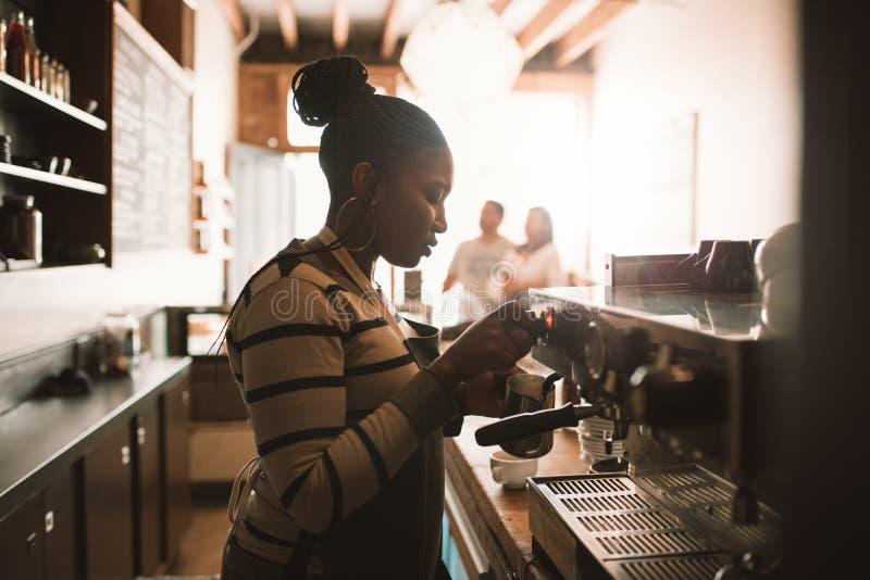Jeune barman africain moussant le lait derrière un compteur de café images stock