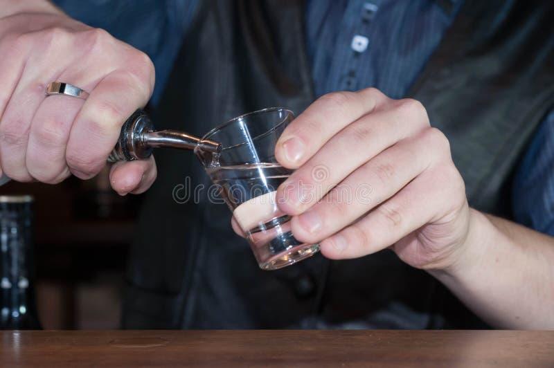 Jeune barman beau dans la chemise bleue, le gilet noir et l'arc rouge donnant le verre avec le cocktail rouge d'alcool photo stock