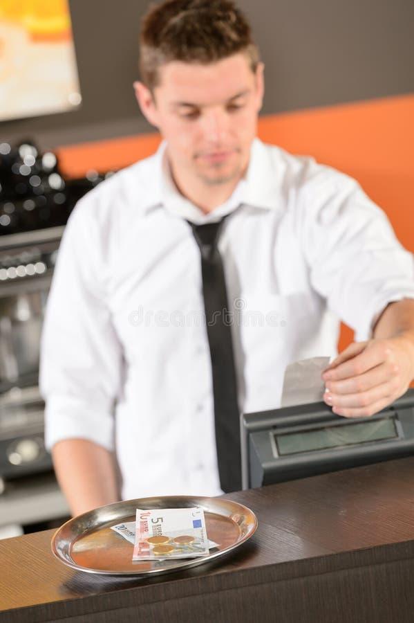 Jeune barman dans l'euro de prise uniforme d'argent liquide photographie stock libre de droits