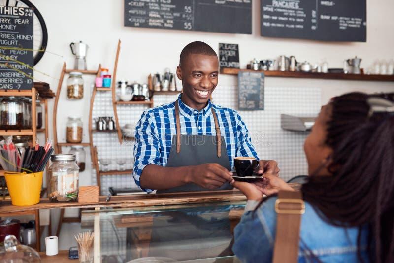 Jeune barman de sourire remettant le café à un client de café photos libres de droits