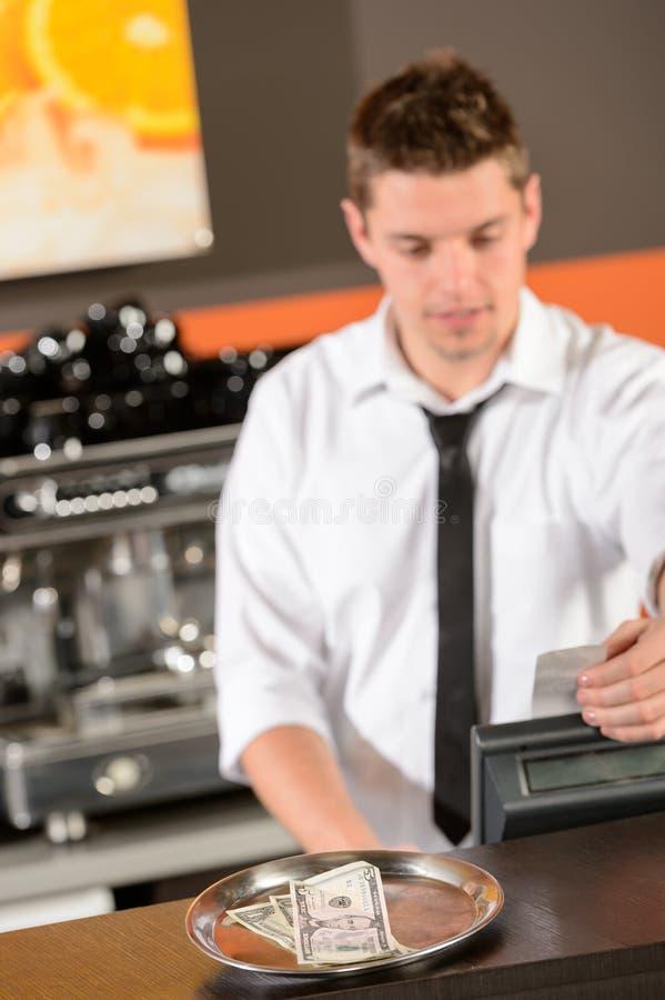 Jeune barman en le dollar de prise uniforme d'argent liquide photos libres de droits
