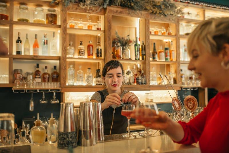 Jeune barman féminin faisant des cocktails derrière un compteur de barre images stock