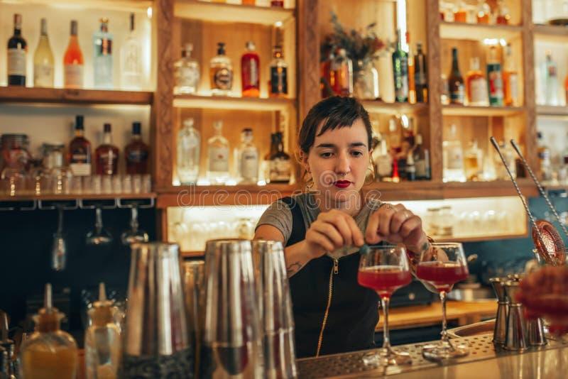 Jeune barman féminin se tenant derrière de contre- cocktails de fabrication d'une barre photos stock