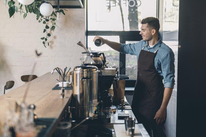 Jeune barman tamisant le café dans le réservoir et le sourire de grain photographie stock
