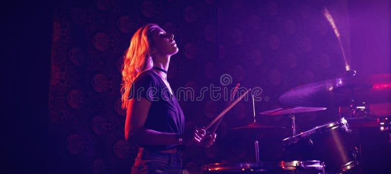 Jeune batteur féminin exécutant dans la boîte de nuit lumineuse photographie stock libre de droits