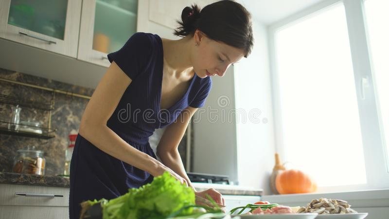 Jeune beau cuisinier de femme coupant les champignons sur le conseil en bois pour la pizza dans la cuisine à la maison image libre de droits