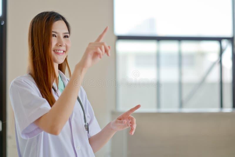 Jeune beau docteur féminin de sourire heureux montrant le secteur vide f images libres de droits