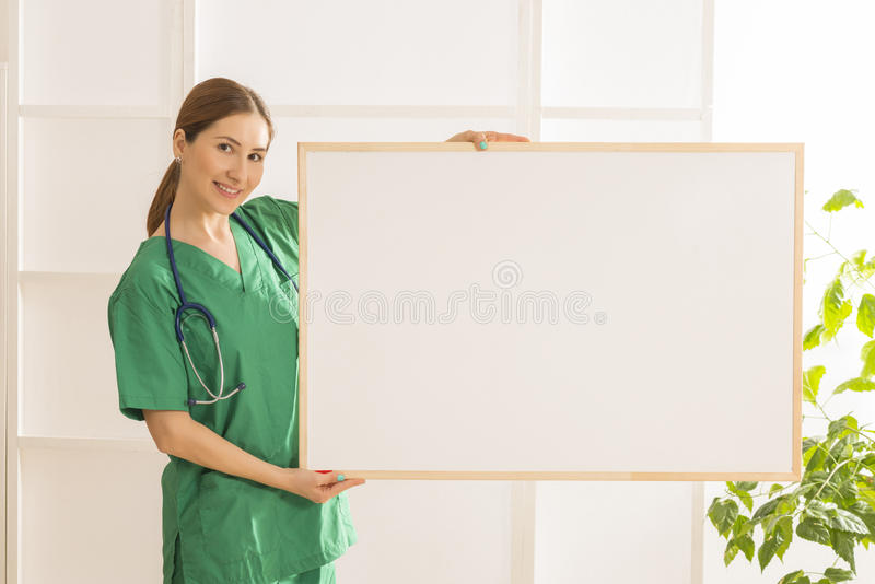 Jeune beau docteur féminin de sourire heureux montrant le secteur vide pour le signe ou le copyspace photo libre de droits