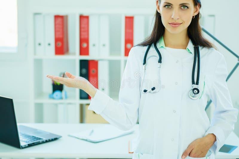 Jeune beau docteur féminin heureux montrant le secteur vide pour le signe ou le copyspace image libre de droits