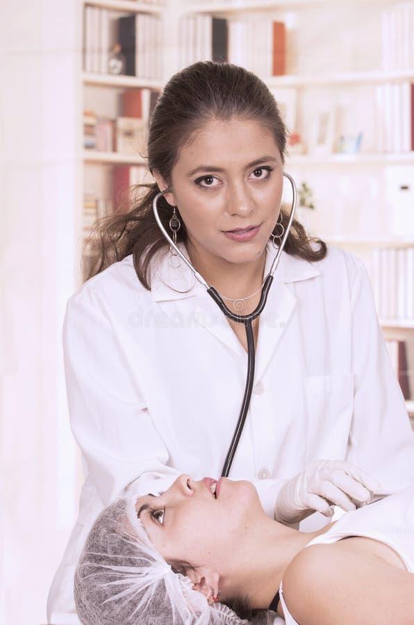Jeune beau docteur féminin vérifiant le patient images libres de droits