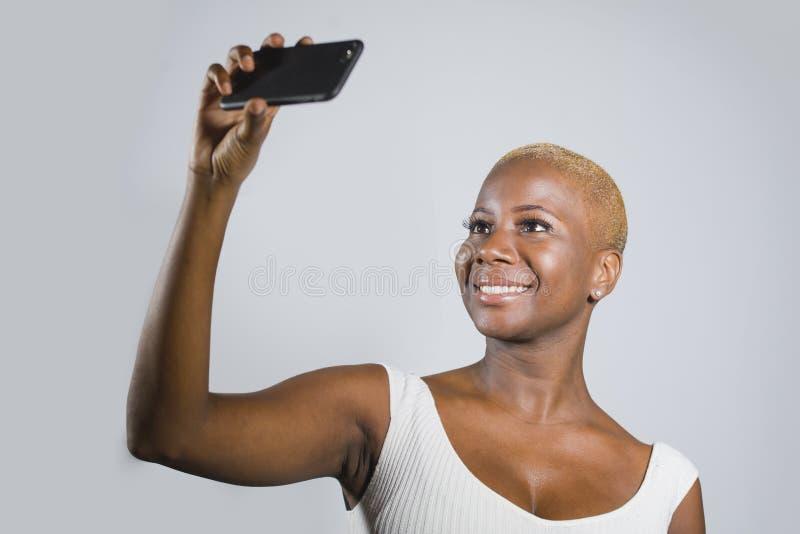 Jeune beau et heureux sourire afro-américain noir de femme excité prenant le portrait de photo de selfie avec le téléphone portab images libres de droits
