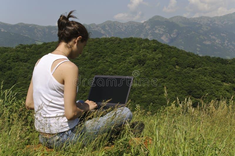 Jeune beau femme à l'aide de son cahier photographie stock libre de droits