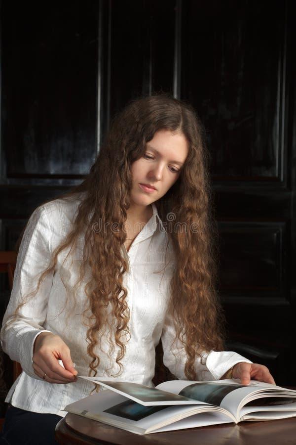 Jeune beau femme affichant un livre photos stock