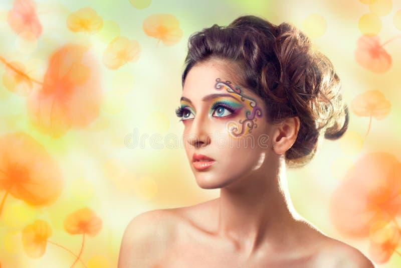 Jeune beau femme au-dessus de fond de fleurs photographie stock