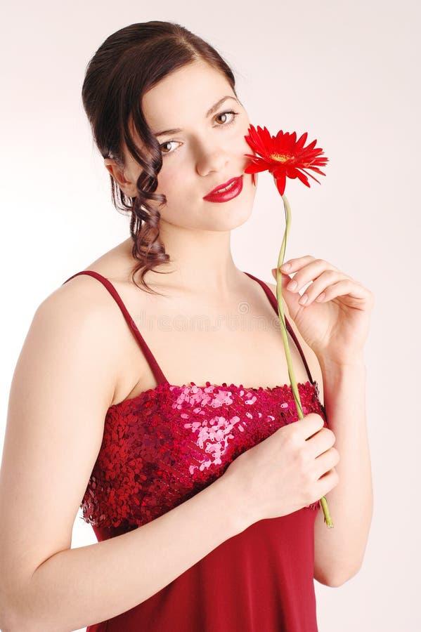 Jeune beau femme avec la fleur rouge image stock