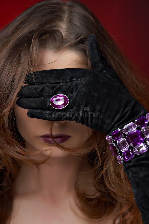 Jeune beau femme avec le bijou violet photographie stock libre de droits