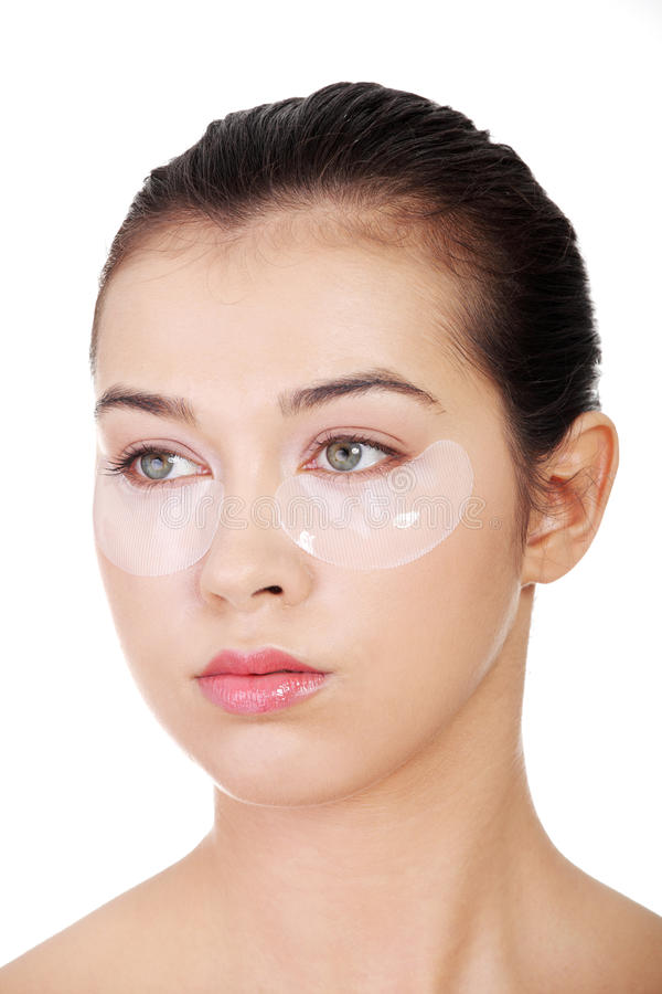 Jeune beau femme avec le masque de levage d'oeil de collagène photo libre de droits