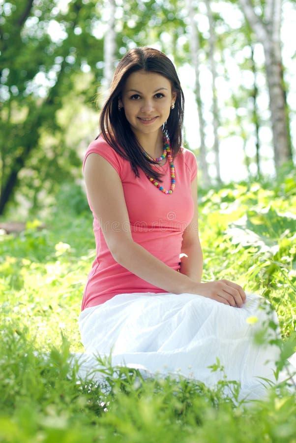 Jeune beau femme dans le dessus rose se reposant à l'extérieur photo stock