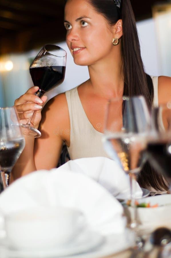 Jeune beau femme goûtant le vin rouge photographie stock libre de droits