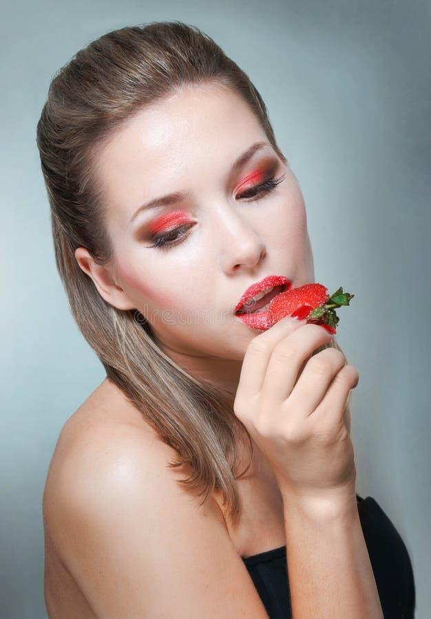 Jeune beau femme mangeant la fraise photo stock