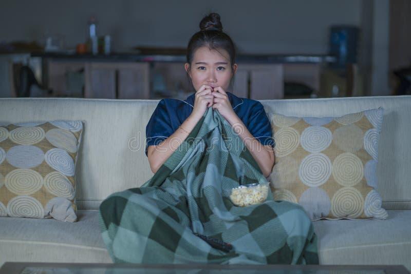 Jeune beau film ou thriller effrayant de observation effrayé et effrayé d'horreur de femme chinoise asiatique mangeant du maïs éc photo stock