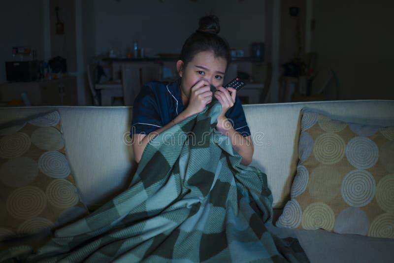 Jeune beau film ou thriller effrayant de observation effrayé et effrayé d'horreur de femme chinoise asiatique mangeant du maïs éc photographie stock libre de droits