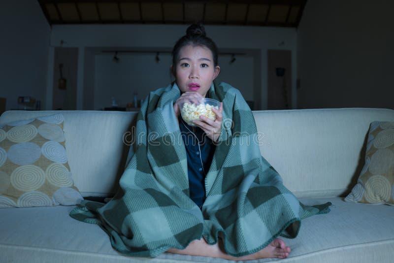Jeune beau film ou thriller effrayant de observation effrayé et effrayé d'horreur de femme coréenne asiatique mangeant du maïs éc photo libre de droits