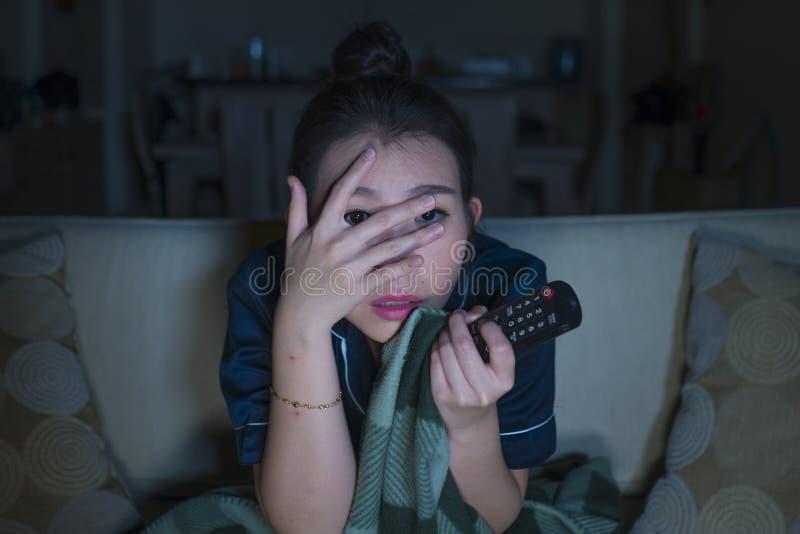 Jeune beau film ou thriller effrayant de observation effrayé et effrayé d'horreur de femme coréenne asiatique mangeant du maïs éc photos libres de droits