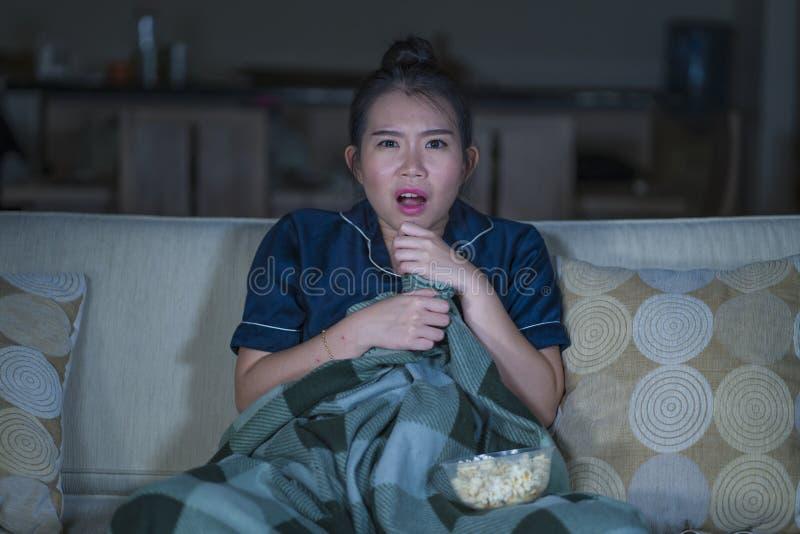 Jeune beau film ou thriller effrayant de observation effrayé et effrayé d'horreur de femme coréenne asiatique mangeant du maïs éc photo stock
