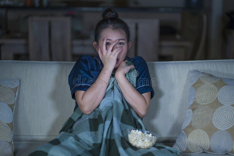 Jeune beau film ou thriller effrayant de observation effrayé et effrayé d'horreur de femme japonaise asiatique mangeant du maïs é photographie stock