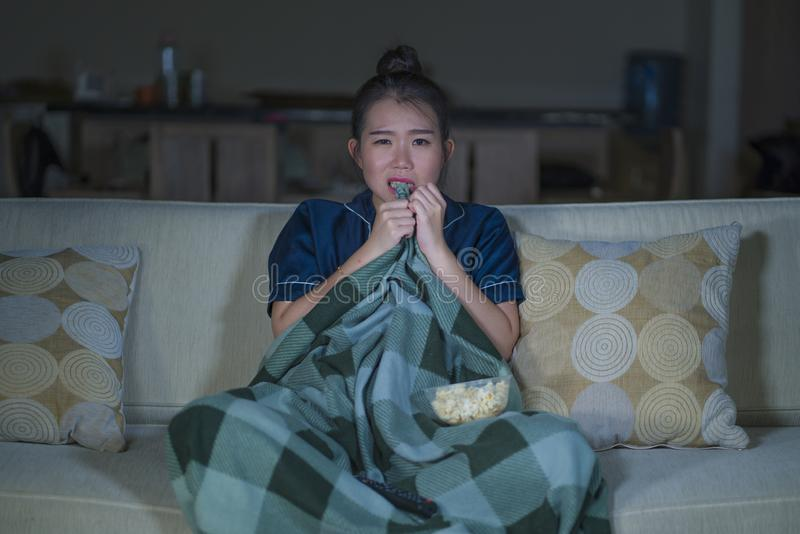 Jeune beau film ou thriller effrayant de observation effrayé et effrayé d'horreur de femme japonaise asiatique mangeant du maïs é images stock