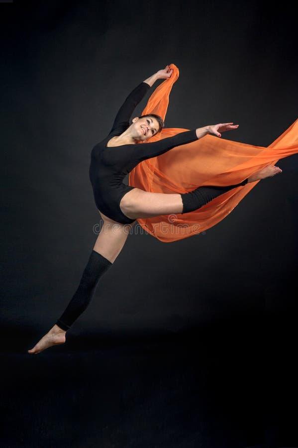 Jeune beau gymnaste d'athlète de femme dans le mouvement sur le backgro noir photographie stock libre de droits