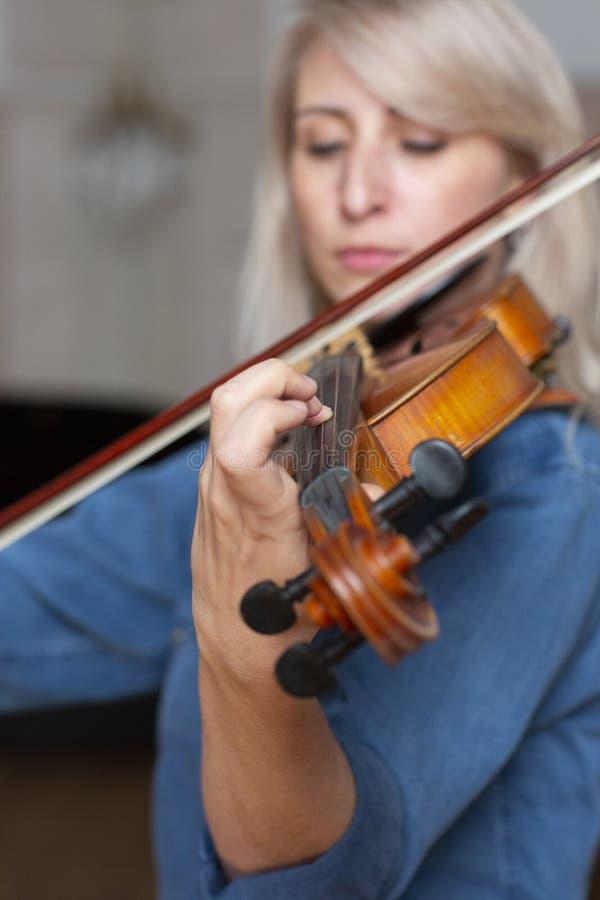 Jeune beau joueur de violon de femme regardant l'appareil-photo au-dessus de l'instrument sur son arc de participation d'épaule photographie stock