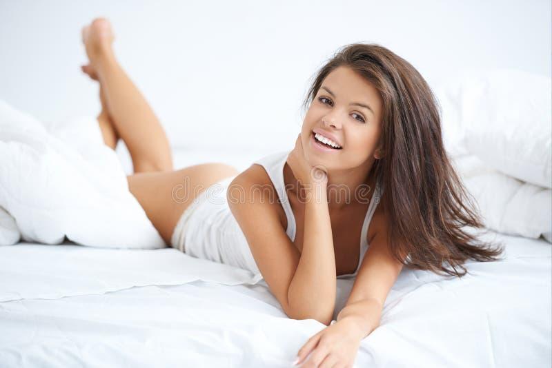 Jeune beau mensonge de femme enclin sur le lit blanc photographie stock libre de droits