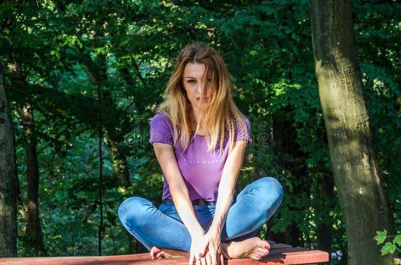 Jeune beau modèle de fille dans les jeans et un T-shirt avec de longs cheveux blonds et sourires tristes posant d'un air songeur  image libre de droits